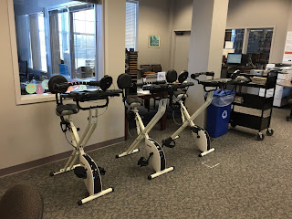 Row of three stationary bikes with laptop workstations arranged against a wall in an office-building setting