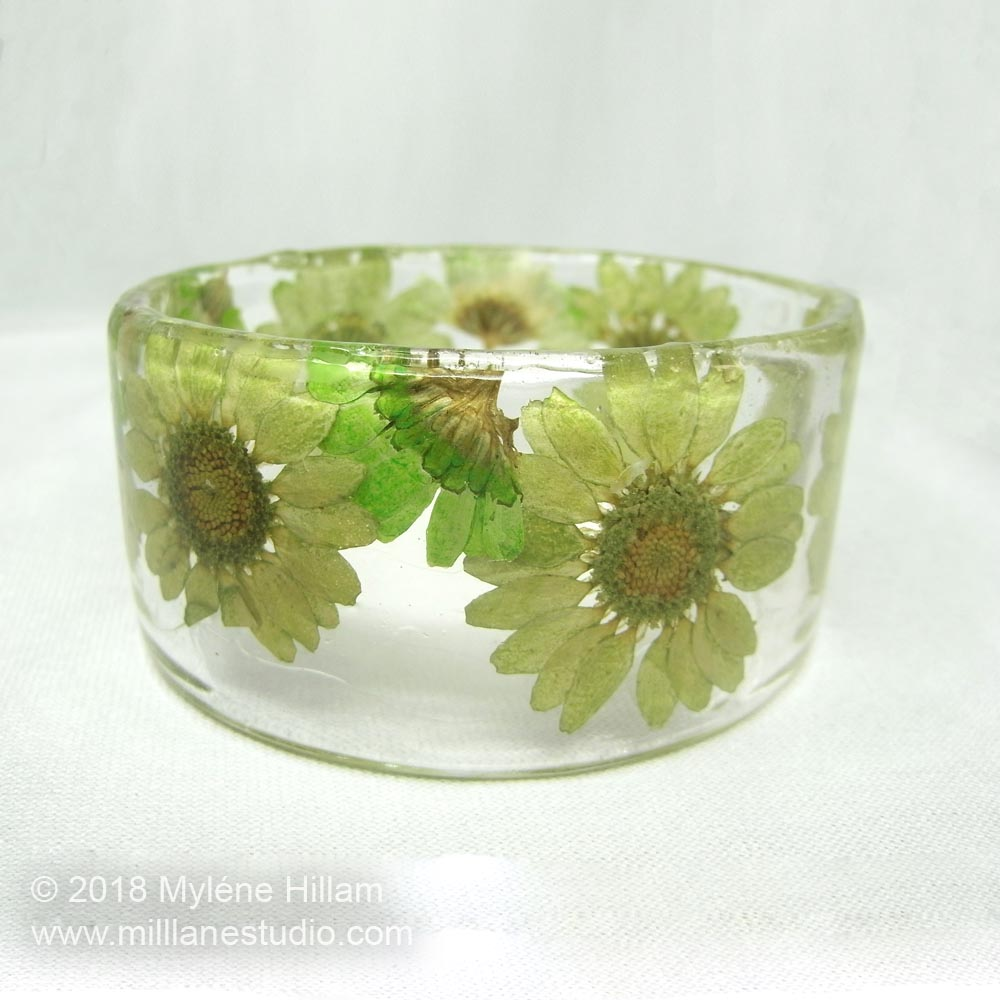 Dried and dyed green daisies embedded in a resin bracelet