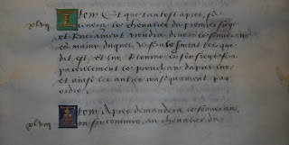 A page of handwritten text with colored initials.