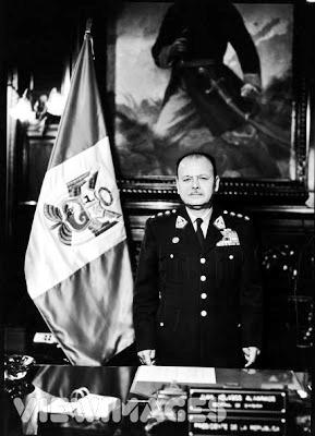 Foto de Juan Velasco Alvarado posando junto a la bandera peruana