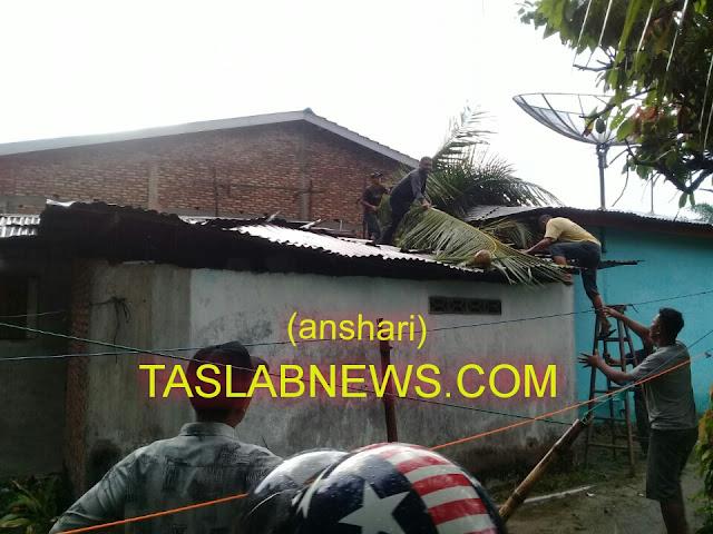 Warga membantu memotong pohon kelapa yang menimpa rumah Wak Ulong.