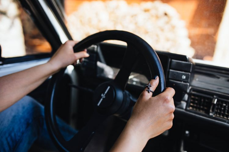 woman on a driving lesson holding a steering wheel
