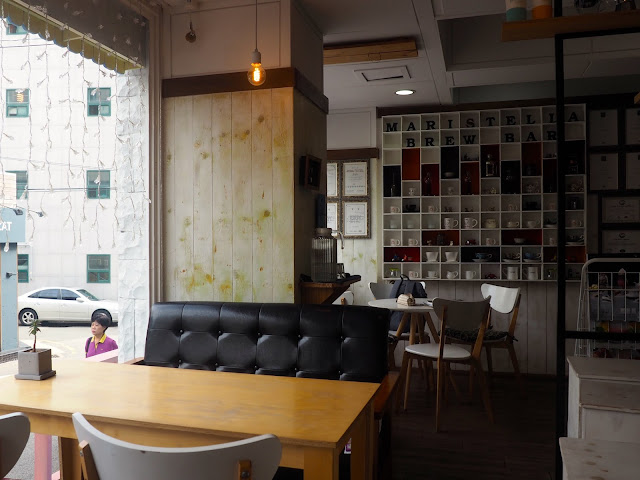 Cafe interior with tables, chairs, sofas and shelves of coffee cups in Marisstella cafe in Myeongnyun, Busan, South Korea