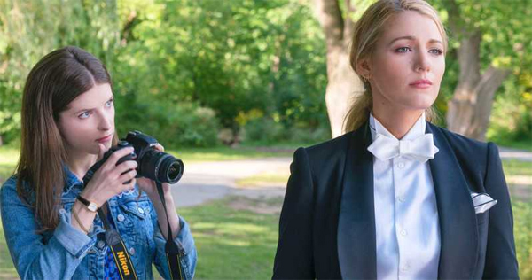 screenshot from the film A Simple Favor, showing Anna Kendrick holding a camera and looking at Blake Lively
