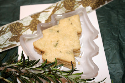 Stacked baked rosemary shortbread Christmas tree cookies on a small plate shaped like a Christmas tree.