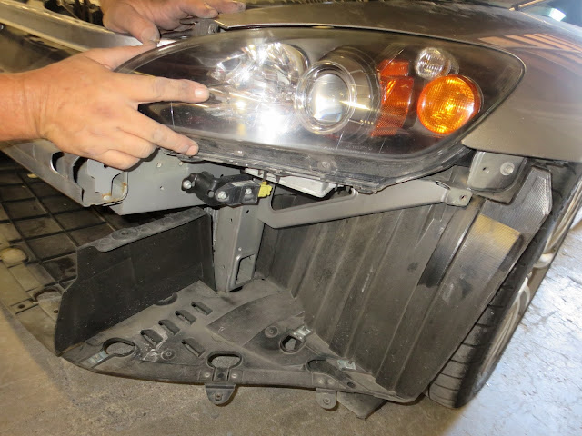Car with bumper off and headlamp being removed for repairs.