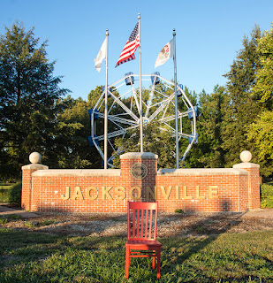 Red chair in front of the the brick Jacksonville sign, three flags flying in front of the Big Eli Ferris wheel in Community Park