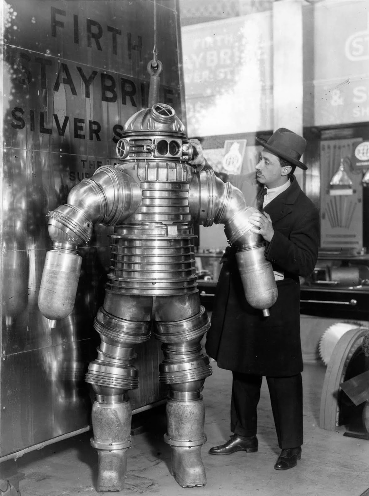 Inventor J. S. Peress explains the workings of his new rustless diving suit, made of Staybrite Silver Steel, at the Olympia Shipping Exhibition in London. The suit weighs 550 pounds and can work at a depth of 650 feet.