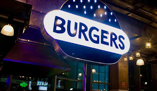 A large white rounded rectangular sign with burgers in dark black font with small circular lights behind it on a dark background