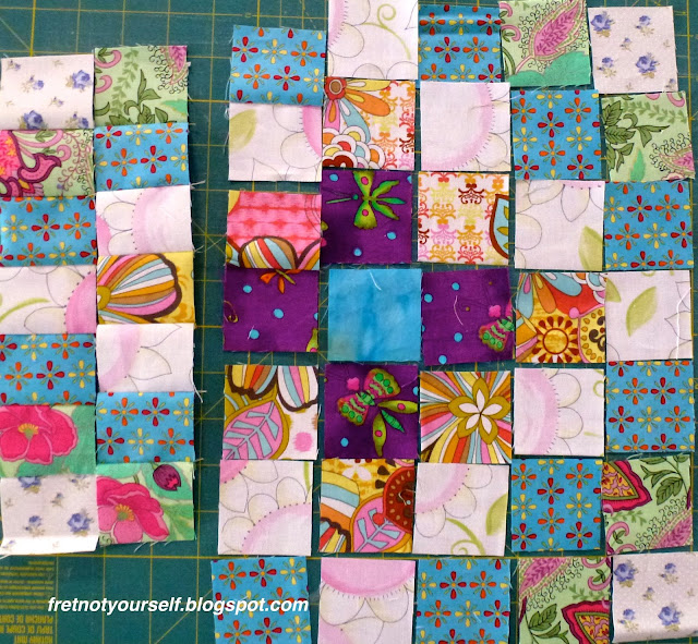 The first block, a Mini-Trip Around the World, is laid out with fabrics encircling the center square.