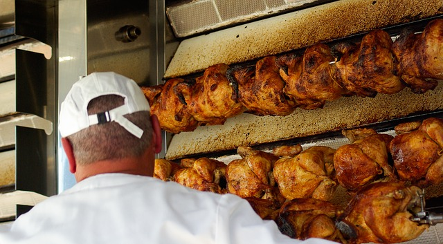 Store Personnel Roasting Several Chickens on a Commercial Spit