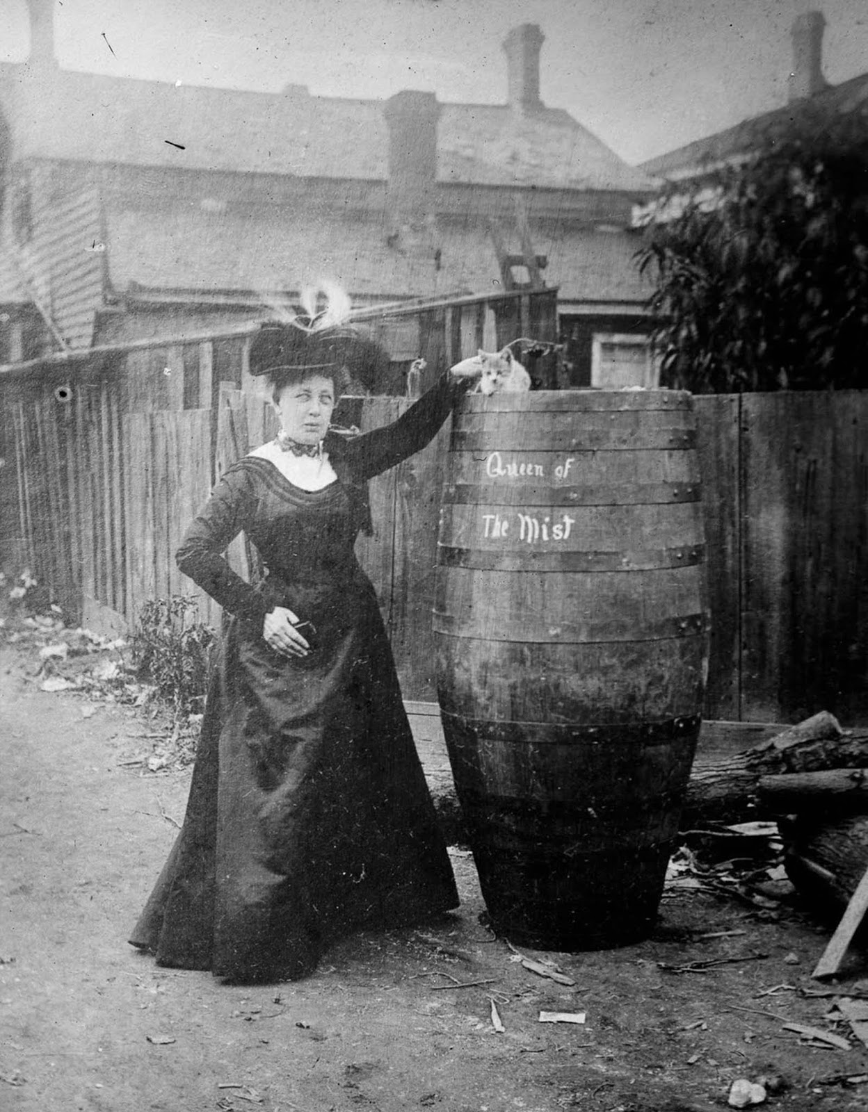 Annie Edson Taylor poses with her cat and the barrel she rode over the falls. 1901.