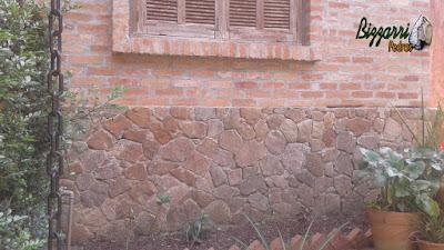 Base da casa com o revestimento de pedra moledo com a parede de tijolo a vista em condomínio em Atibaia-SP.