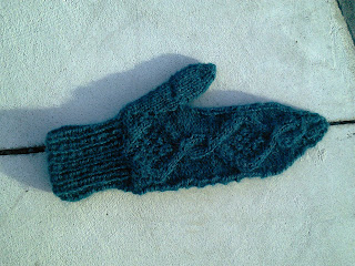 A mitten knit in deep turquoise yarn laying flat.  There is a cable pattern on the back of the hand.