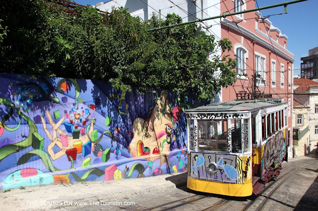 A yellow tram riding up a steep and narrow hill next to a Street art mural of a woman.
