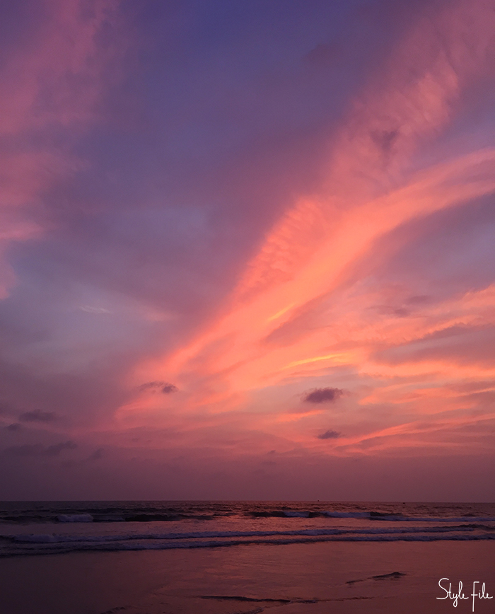 Image of a sunset by the sea in Goa with the sky in shades of orange, peach, purple and gold