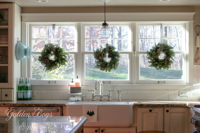 Trader Joes wreaths over farmhouse kitchen sink in Christmas kitchen - www.goldenboysandme.com