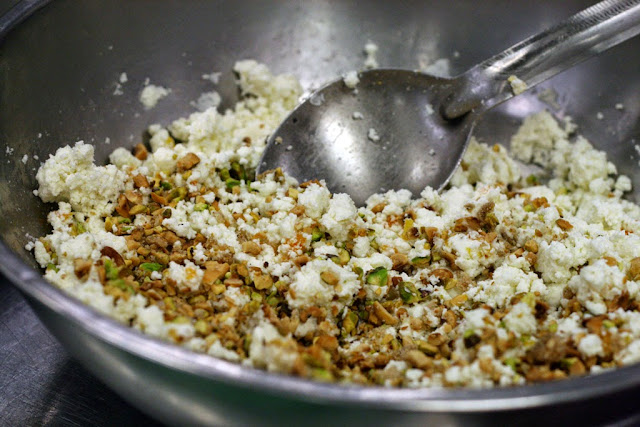 Goat Cheese mixed with roasted nuts and a sprinkle of salt in a bowl.