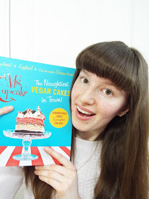 Ellie smiling brightly, holding up a Ms Cupcake vegan baking book, pointing to the cake on the cover with practically a sparkle in her eyes
