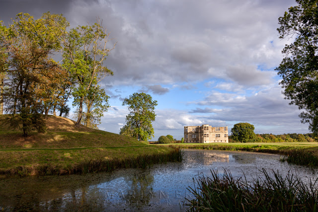 Lyveden Hall and mound reflected in the moat in the autumn sunshine