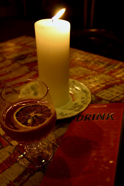 A Blood Orange and Whiskey Sours cocktail sits on a table in the Cosy Club, alongside a candle and a copy of the drinks menu