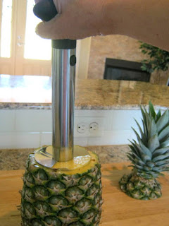 Holding the pineapple with one hand, line up the cutter with the core of the pineapple then start turning. You'll need to apply just a bit of pressure.  Continue turning and slicing until you reach almost to the bottom of the pineapple.