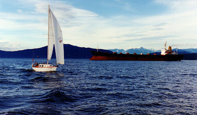 32 foot Discovery sailboat cruises past a freighter in English Bay