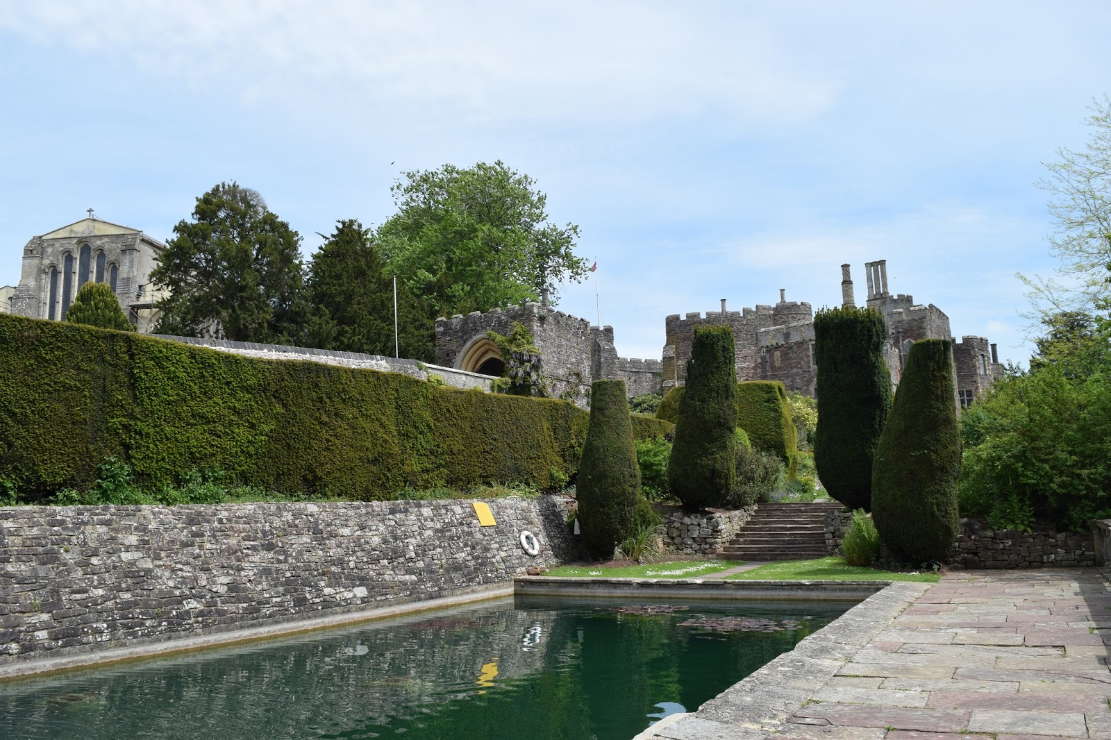 from the gardens of the castle. in front of me is a large pool. in the background the castle and the church can be seen behind the trees