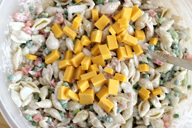 creamy tuna pasta salad in bowl with spoon ready to mix in cheese