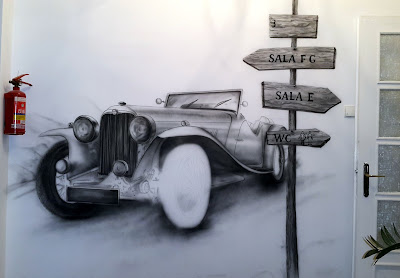 Malowanie graffiti na ścianie, mural przedstawia samochód w stylu retro, mural w sepii
