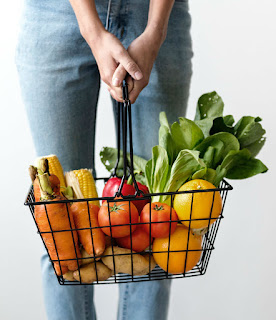 Woman holding wire basket full of fruit and vegetables