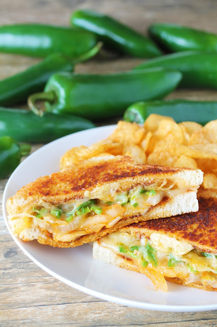 These grilled cheese sandwiches are cut in half, bursting with the flavor of sauteed onion, melted pepperjack cheese and all the spice from jalapenos and sriracha with a little crunch from a side of jalapeno chips. Served on a plate with a side of jalapeno potato chips.
