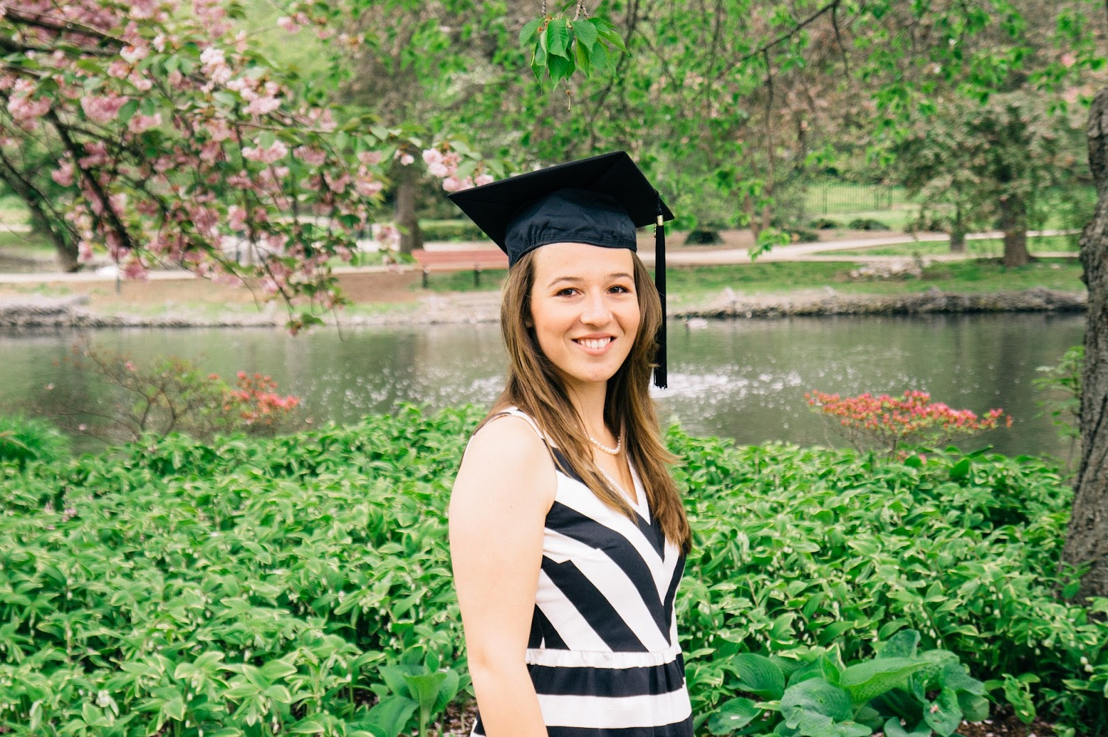 Graduate wearing her cap in front of pink, flowering trees and pond.