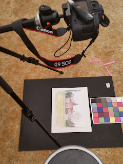 a photo showing the placement of the camera, the artwork, the remote trigger, the tripod setup, and a black art board on the floor for copying the art digitally.