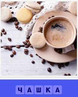 на столе стоит чашка с кофе и разбросаны зерна для кофе