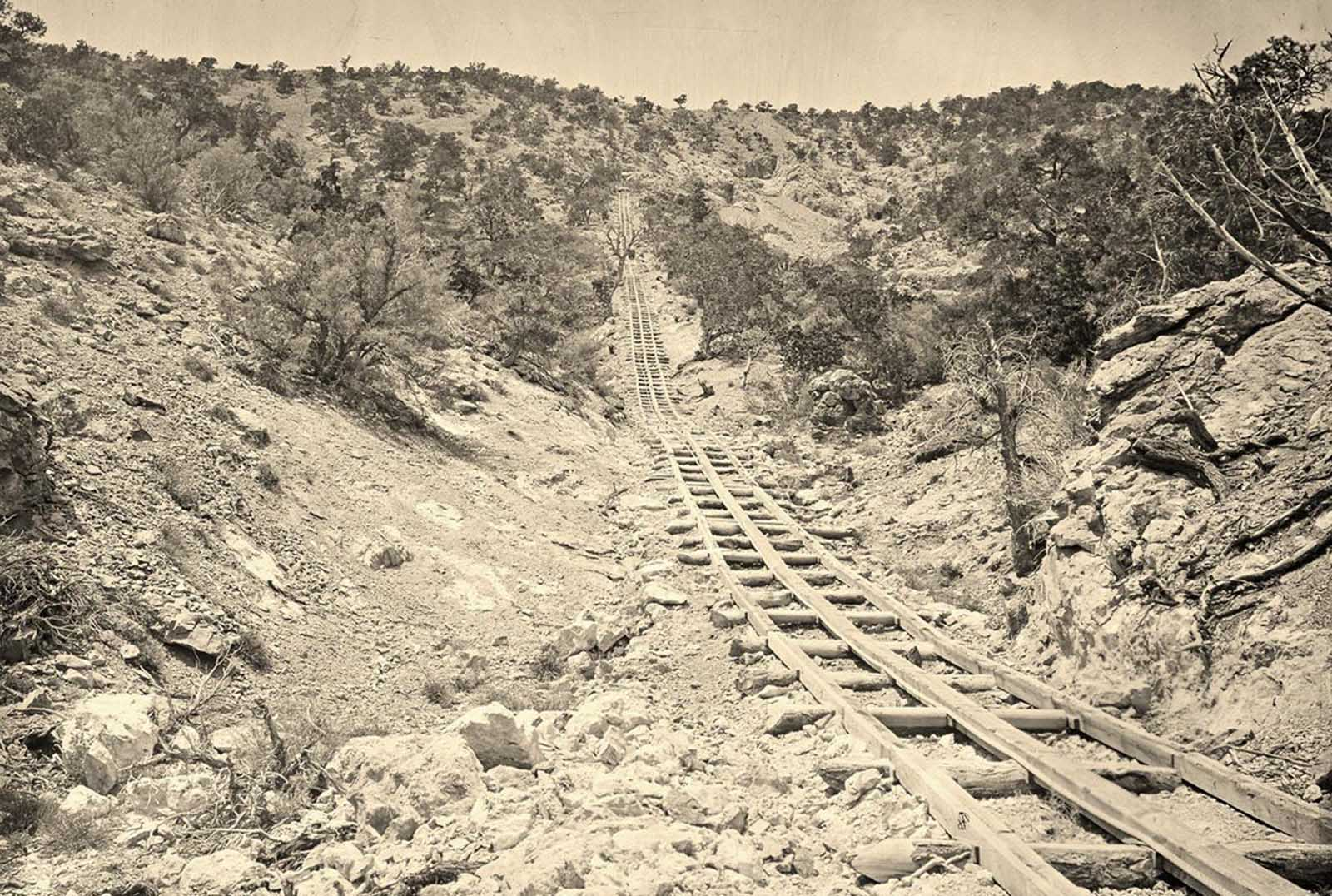A wooden balanced incline used for gold mining, at the Illinois Mine in the Pahranagat Mining District, Nevada in 1871. An ore car would ride on parallel tracks connected to a pulley wheel at the top of tracks.