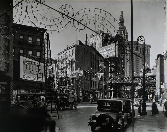 Oak and New Chambers Streets, Manhattan. October 28, 1935. Notes: Code: III.B.1. Exhibited: Modern Vision #57 Festive lights in curlicue designs arch over street, men with tall ladder, wagons, cars, billboards; 'el' and Municipal Bldg. just visible. Source: Changing New York / Berenice Abbott. Repository: The New York Public Library. Photography Collection, Miriam and Ira D. Wallach Division of Art, Prints and Photographs.