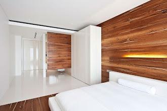 Duvarları ve tabanının bir kısmı geniş ağaç lambri tahtalar ile kaplanmış modern bir yatak odası