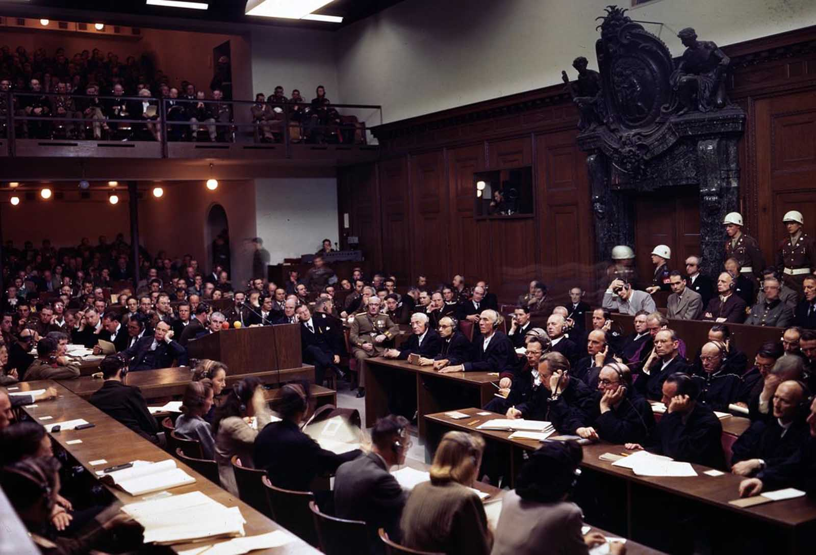 The interior of the courtroom of the Nuremberg War Crimes Trials in 1946 during the Trial of the Major War Criminals, prosecuting 24 government and civilian leaders of Nazi Germany. Visible here is Hermann Goering, former leader of the Luftwaffe, seated in the box at center right, wearing a gray jacket, headphones, and dark glasses. Next to him sits Rudolf Hess, former Deputy Fuhrer of Germany, then Joachim von Ribbentrop, former Nazi Minister of Foreign Affairs, Wilhelm Keitel, former leader of Germany's Supreme Command (blurry face), and Ernst Kaltenbrunner, the highest ranking surviving SS-leader. Goering, von Ribbentrop, Keitel, and Kaltenbrunner were sentenced to death by hanging along with 8 others -- Goering committed suicide the night before the execution. Hess was sentenced to life imprisonment, which he served at Spandau Prison, Berlin, where he died in 1987.
