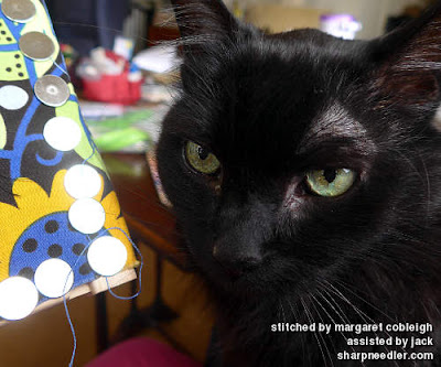 Black cat helping with bead embroidery