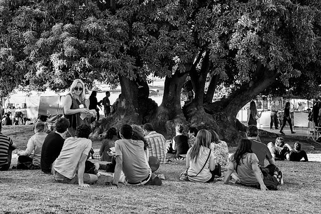 Gente sentada  en el pasto reunida en Recoleta.Blanco y negro