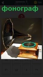 на столе стоит старинный фонограф с пластинкой