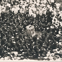 A black and photograph of figures in caps and gowns, taken from above.
