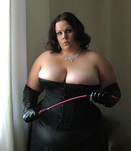 woman dressed in black corset holds a red whip, curves