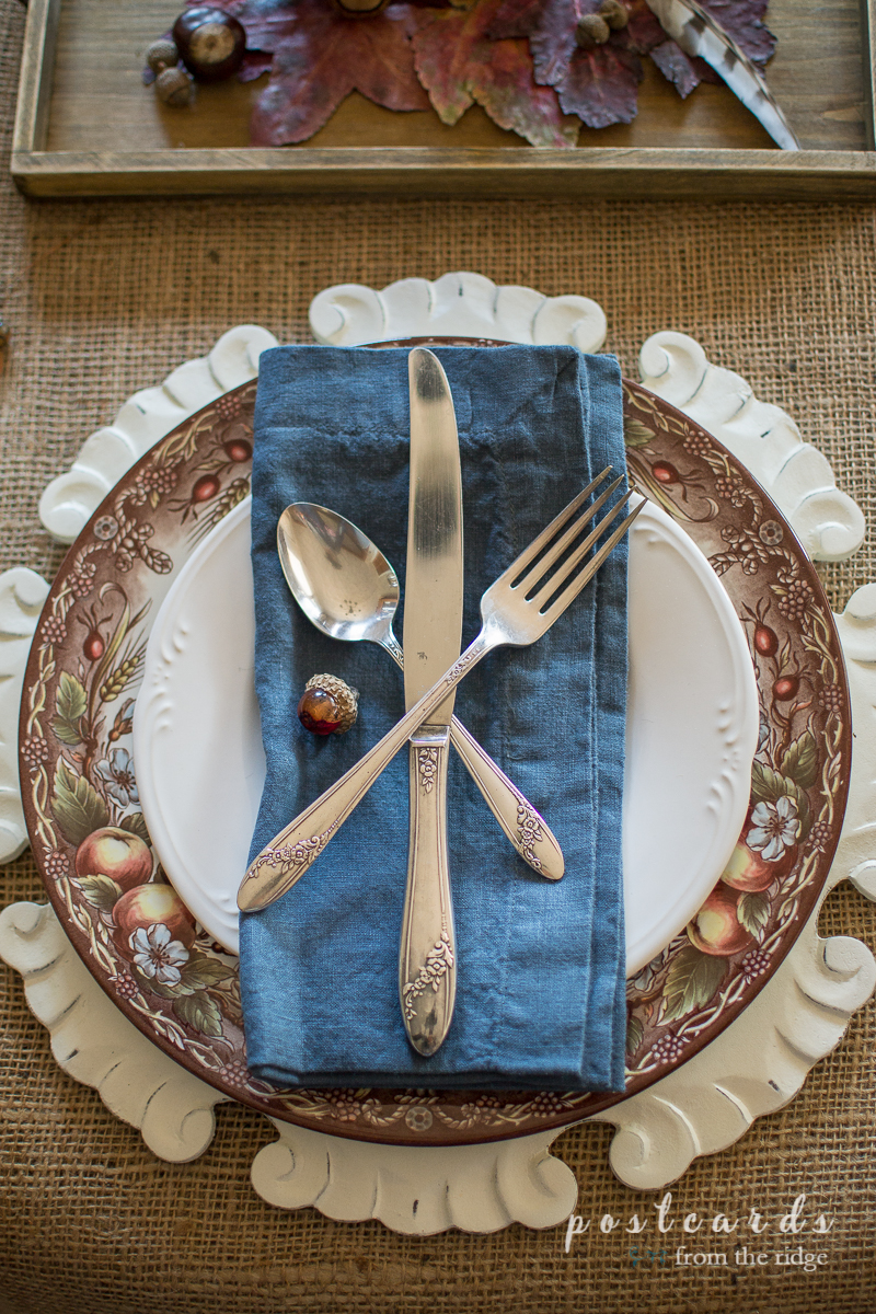 fall table setting with blue napkin and vintage silverware