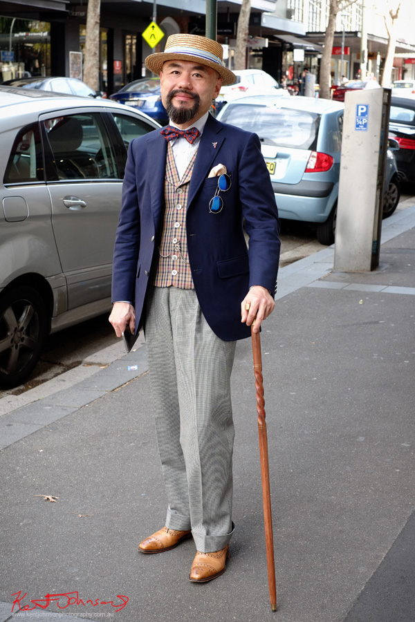 Gentleman in Darlinghurst with boater and cane; Navy Jacket, check vest and a real bow tie. Men of Street Fashion Sydney.