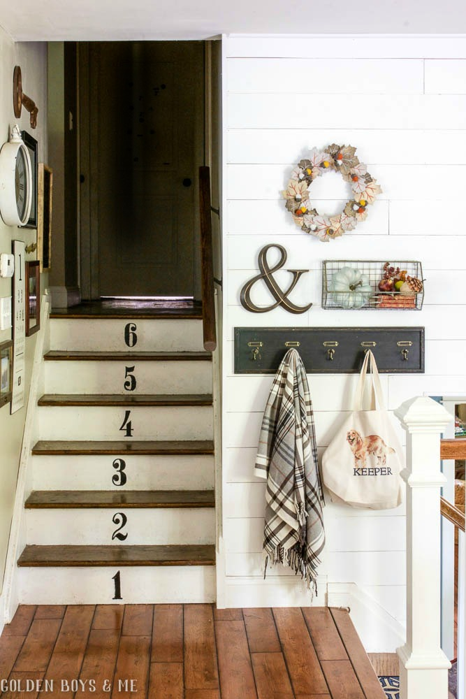 Gallery wall with fall decor, numbered stairs and planked wall