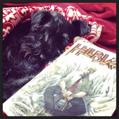 Duffy snuggles up in a red blanket nest, a trade paperback copy of Hellblazer: Original Sins in front of him. The book's cover features a blonde white man holding a beer. He sits in front of an indistinct fallen god-thing.