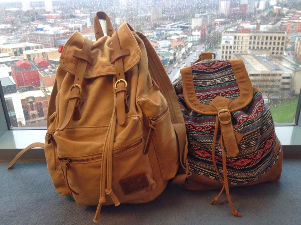 Two brown rucksacks in front of a large window. The smaller rucksack has multi coloured thread running through the body of it.