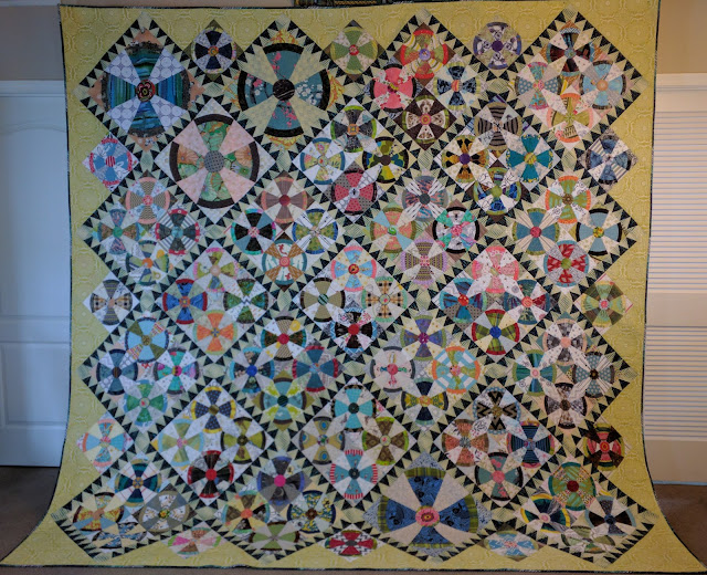 This scrap quilt features many conversational prints, scale change of block, sawtooth sashing